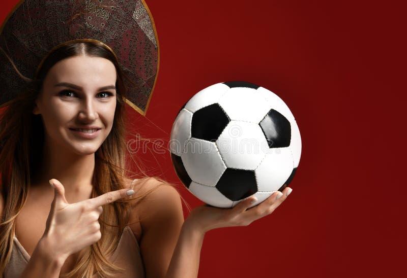 Ruusian-Art Fansport-Frauenspieler im kokoshnik Grifffußball das glückliche lächelnde Lachen feiernd lizenzfreie stockfotografie