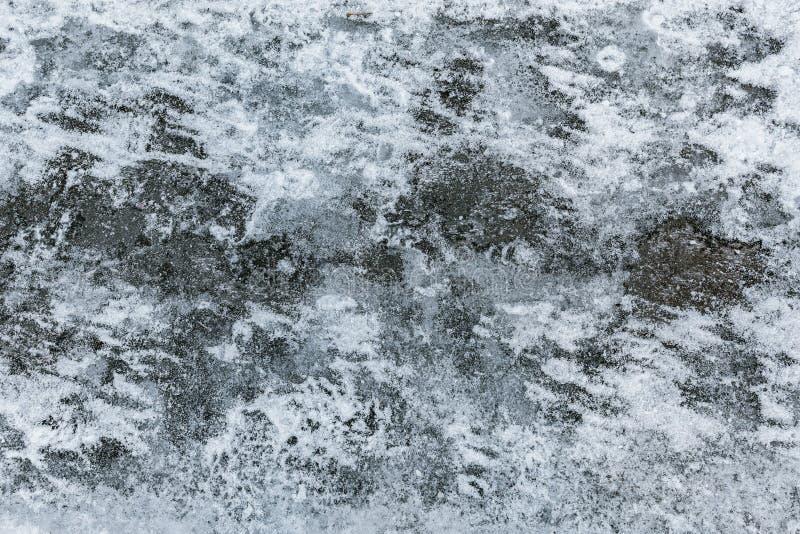 Ruw asfalt met smeltend sneeuw en ijs stock afbeeldingen