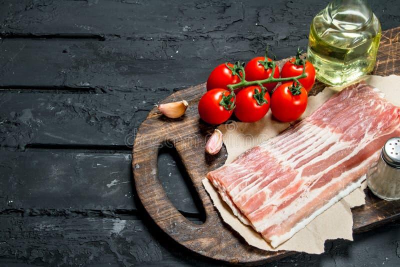 Ruw bacon met tomaten en kruiden royalty-vrije stock foto