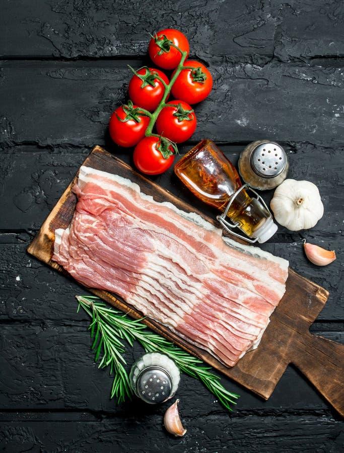 Ruw bacon met tomaten en kruiden royalty-vrije stock afbeelding