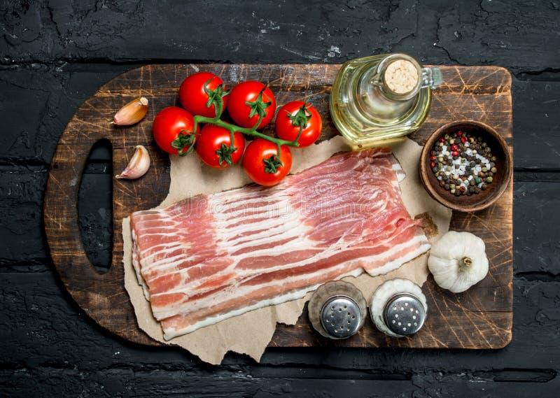 Ruw bacon met tomaten en kruiden stock afbeelding