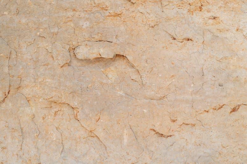Ruw de textuur van de rotssteen geeloranje natuurlijk zandsteen als achtergrond stock afbeelding