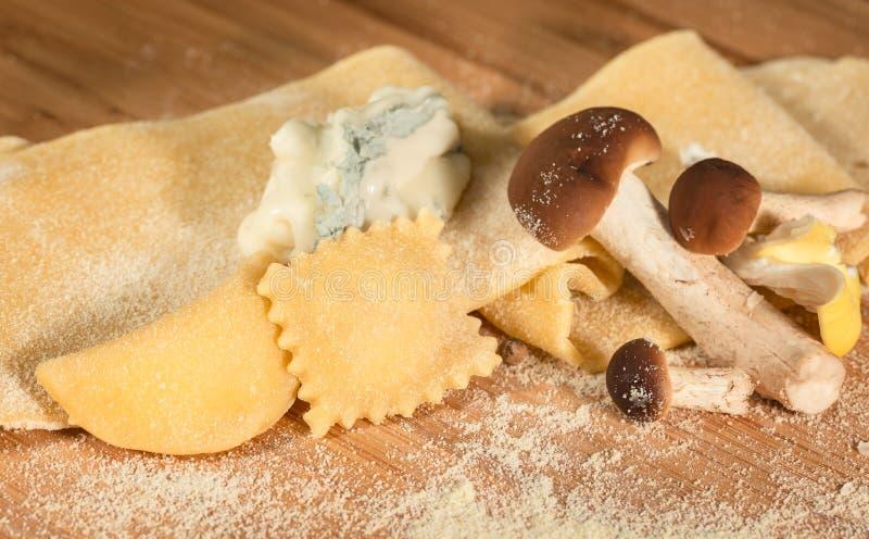 Ruw deeg en Italiaanse eigengemaakte ravioli met gorgonzola-kaas en verse die paddestoelen, op de houten die lijst wordt geplaats stock afbeeldingen