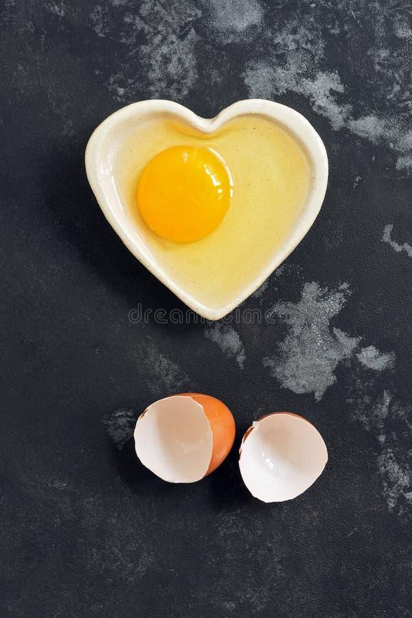 Ruw die ei in een kom en een eierschaal op een donkere concrete achtergrond wordt gebroken Vlak leg royalty-vrije stock afbeelding