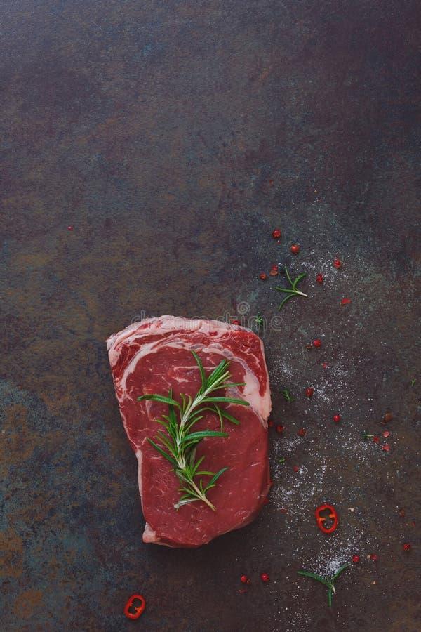 Ruw die rundvleeslapje vlees op steenachtergrond met rozemarijn wordt versierd stock afbeelding
