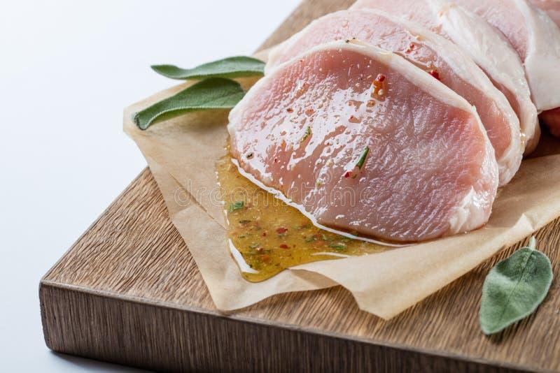 Ruw die varkensvlees escalope met sause van honing en kruiden wordt gemaakt stock fotografie