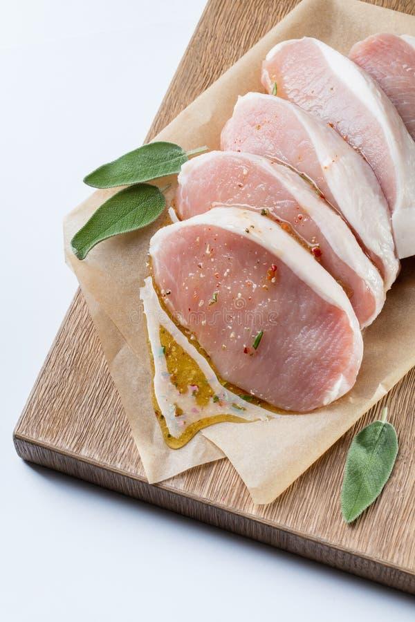 Ruw die varkensvlees escalope met sause van honing en kruiden wordt gemaakt stock afbeelding