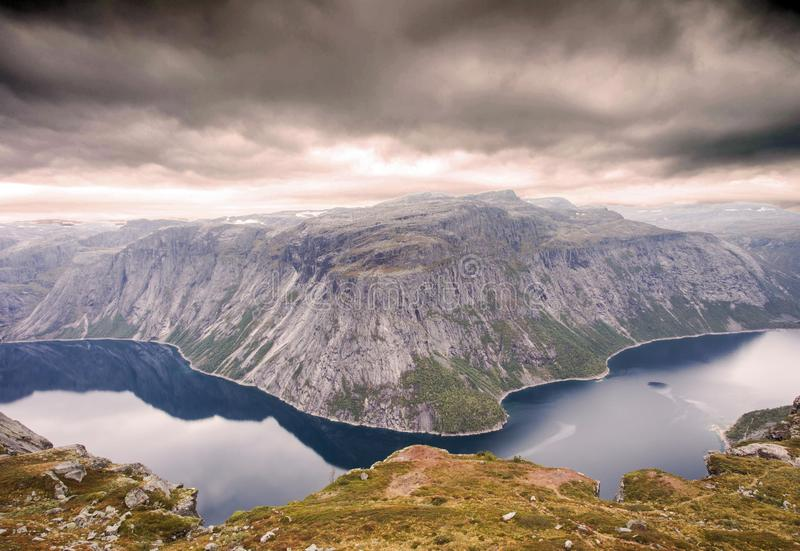 Ruw dramatisch berglandschap in de bewolkte dramatische dag van Noorwegen met kalm meer royalty-vrije stock foto's