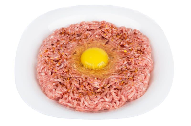 Ruw ei in fijngehakt varkensvlees in plaat stock afbeeldingen
