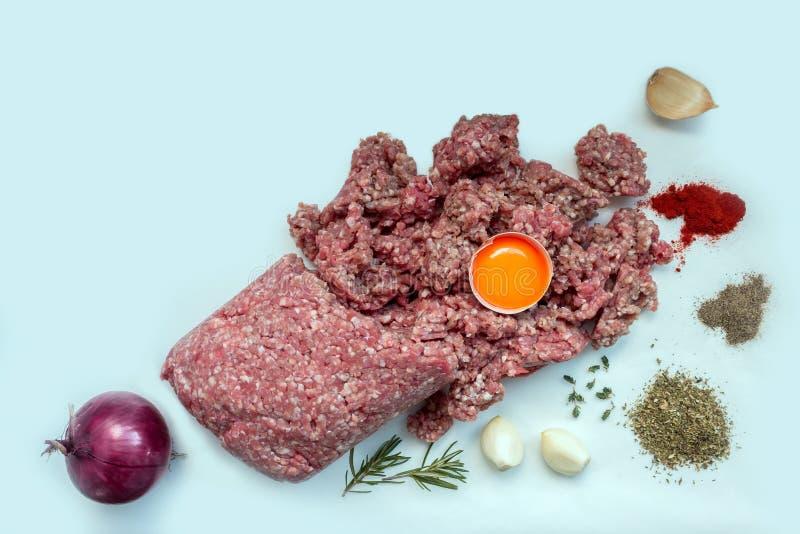Ruw gehakt met peper, ei, kruiden en kruiden voor het koken van koteletten, burgers, vleesballetjes royalty-vrije stock foto