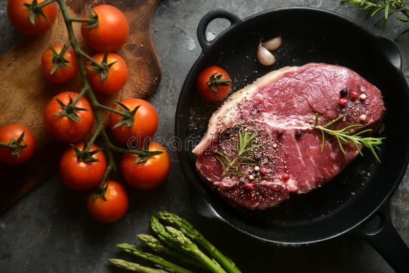 Ruw gemarineerd vlees in ijzerpan, met ingrediënten het omringen de hoogste vlakke mening, legt, horizontaal beeld stock foto's