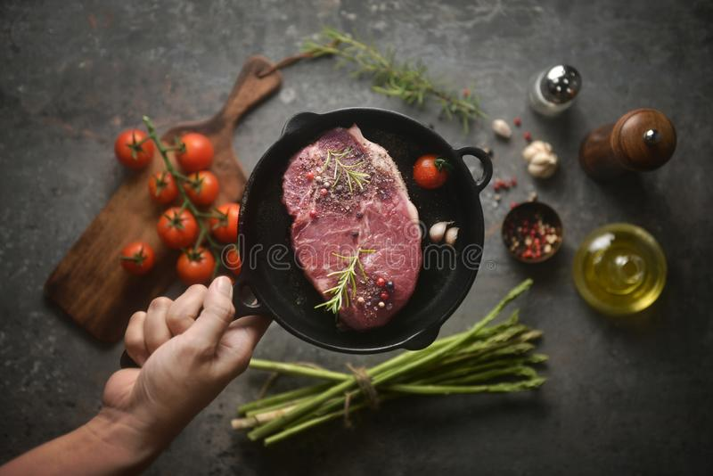 Ruw gemarineerd vlees in ijzerpan op hand, en ingrediënten die op bodemachtergrond omringen Mening van hierboven, horizontaal bee stock foto