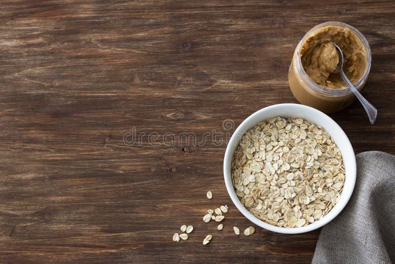 Ruw havermeel in een witte kom met pindakaas, ingrediënten voor een heerlijk gezond ontbijt op een houten achtergrond royalty-vrije stock afbeelding