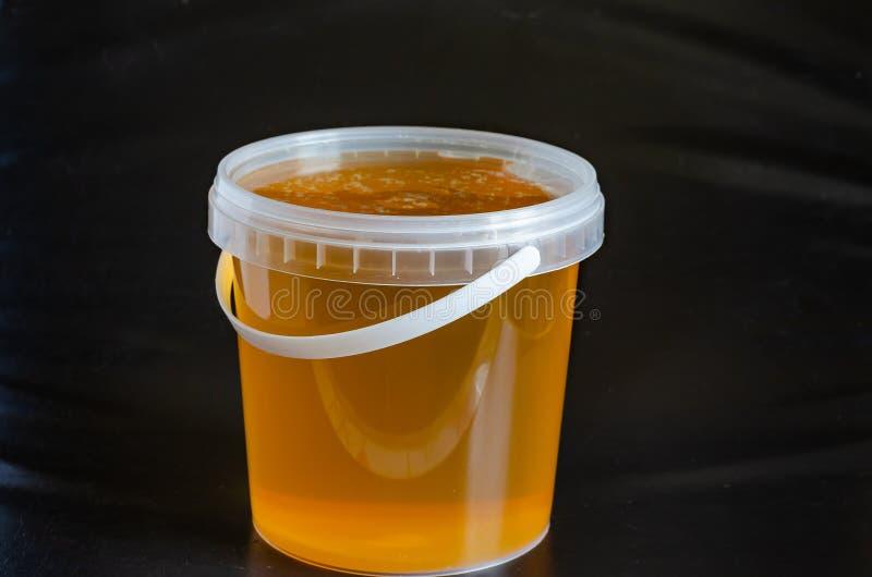 Ruw Honey Freshly oogstte organische natuurlijke honing Een emmer honing op een zwarte achtergrond Macro Het schieten op oognivea stock fotografie