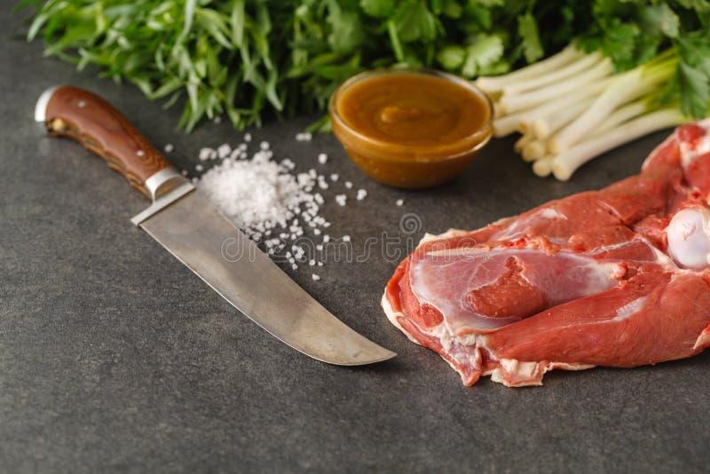 Ruw lamsvlees met kruiden op houten raad over oude houten backgrou stock afbeeldingen