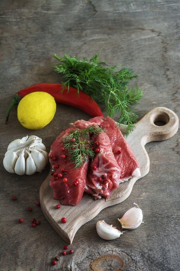 Ruw lamsvlees met kruiden op houten raad over oude houten backgrou stock foto's