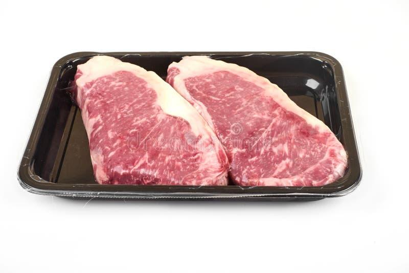 Ruw lapje vlees in een luchtdichte vacuümverpakking op een witte achtergrond stock afbeeldingen