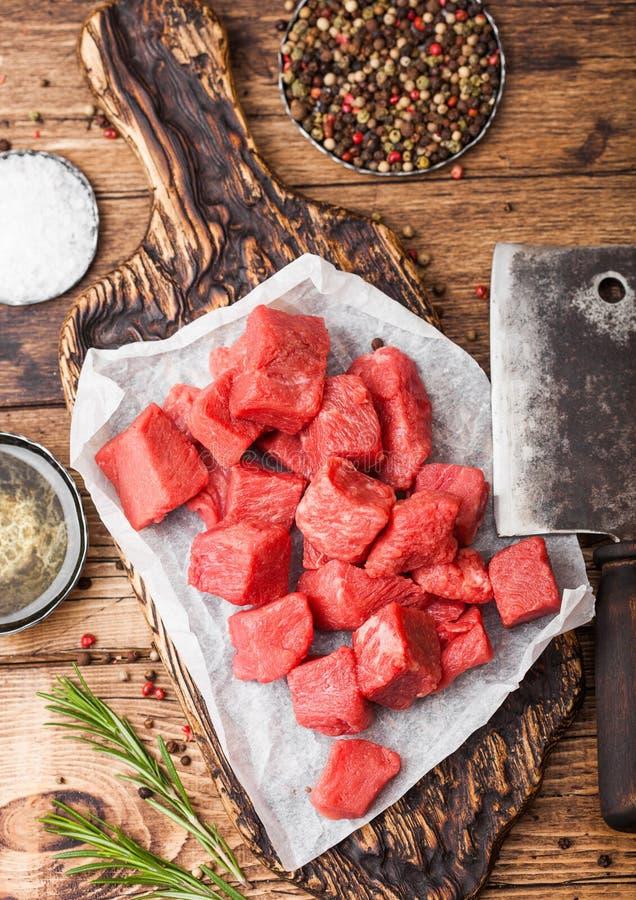 Ruw mager gedobbeld het varkensvleeslapje vlees van het braadpanrundvlees op hakbord met uitstekende vleeshouthakkersbijlen op ho royalty-vrije stock afbeelding