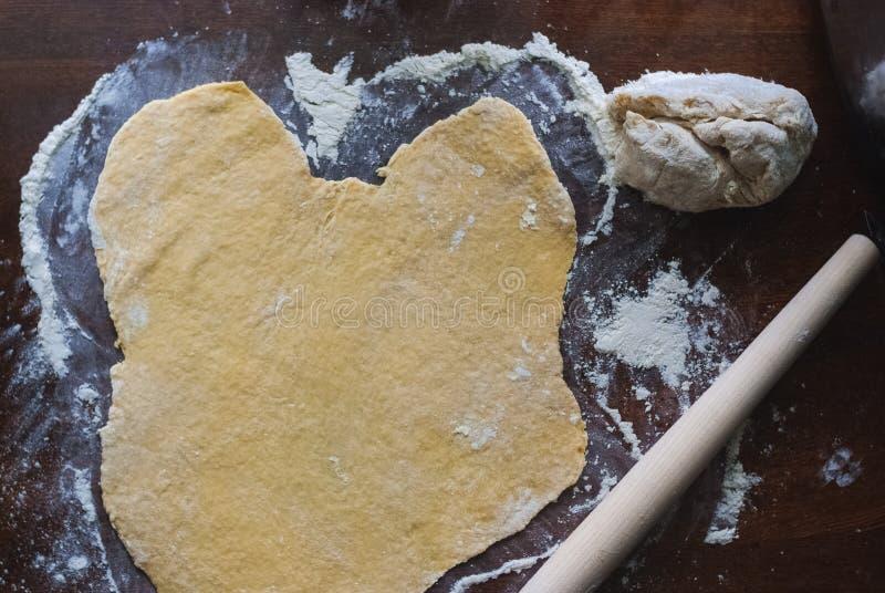 Ruw ongedesemd deeg op keukenlijst, schommelend broodje, selectieve nadruk stock foto
