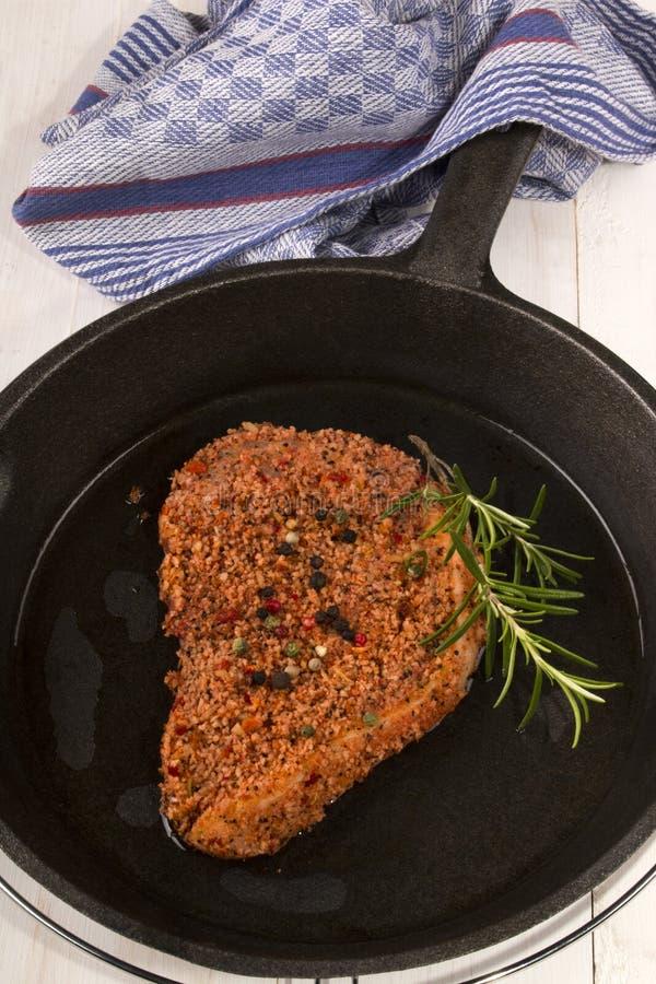 Ruw peppered varkenskotelet in een gietijzerpan stock afbeelding