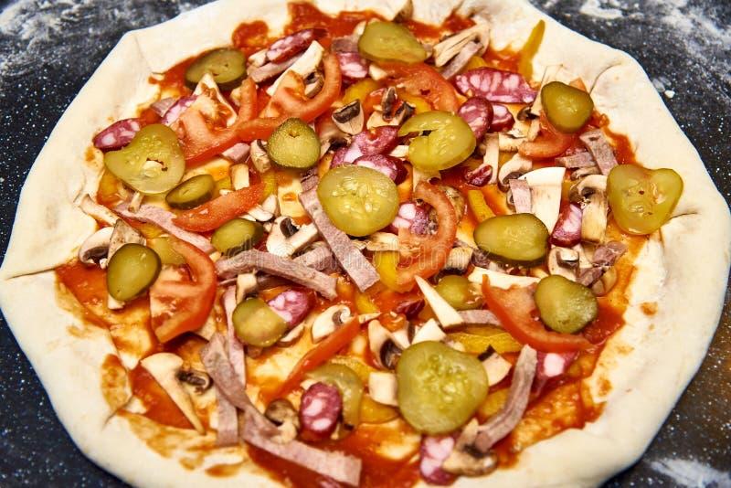 Ruw pizzadeeg met vlees, groenten en sausclose-up stock fotografie