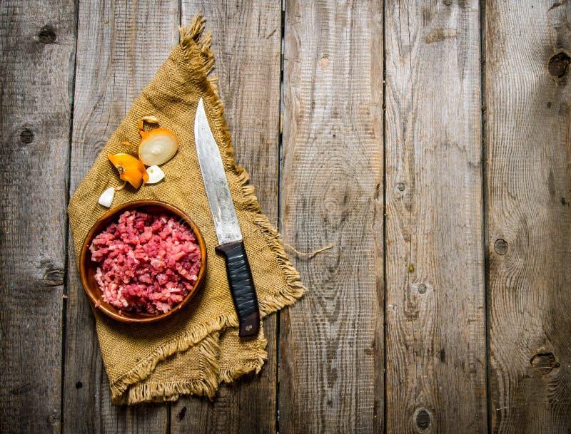 Ruw rundergehakt met een slagersmes en een ui royalty-vrije stock foto's