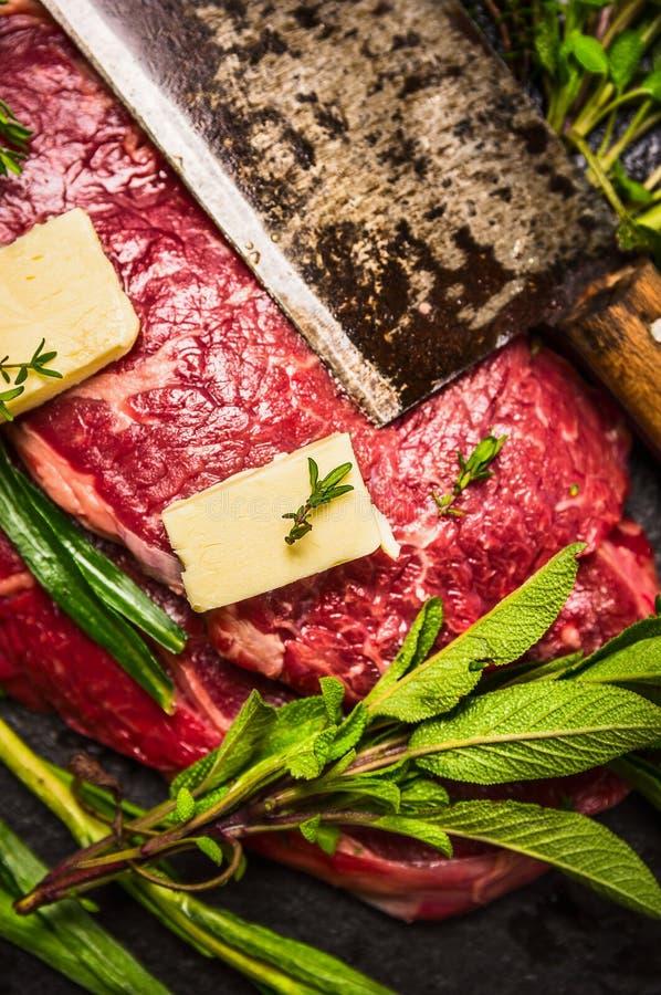 Ruw rundvleesvlees met boter, oud mes en verse kruiden, voorbereiding voor het koken stock afbeelding
