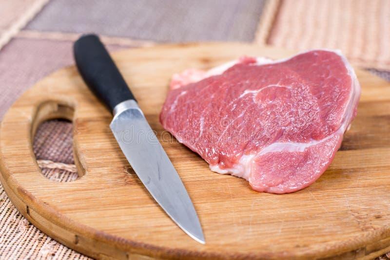 Ruw rundvleesvlees op de knipselraad met mes stock afbeeldingen