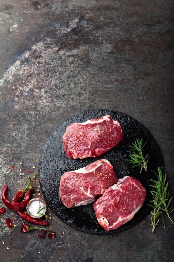 Ruw rundvleesvlees Verse lapjes vlees op leiraad op zwarte achtergrond stock afbeelding