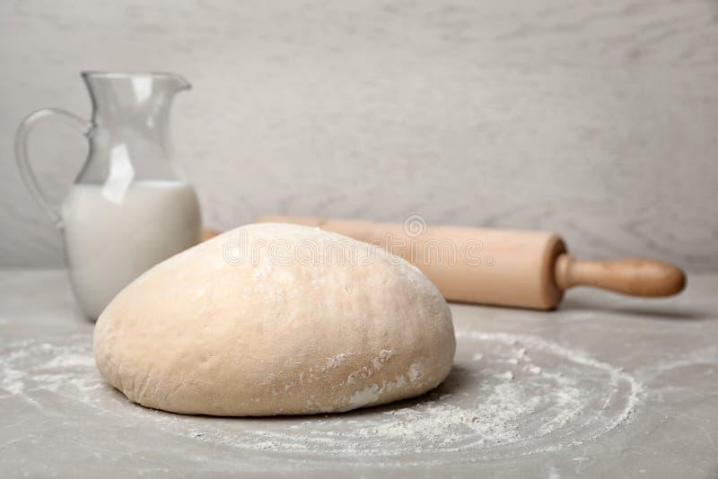 Ruw tarwedeeg, waterkruik met melk en deegrol op grijze lijst stock foto