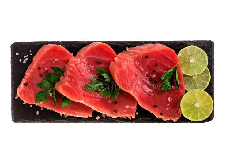 Ruw tonijnlapje vlees met citroen en kruiden op zwarte lei cutboard royalty-vrije stock foto