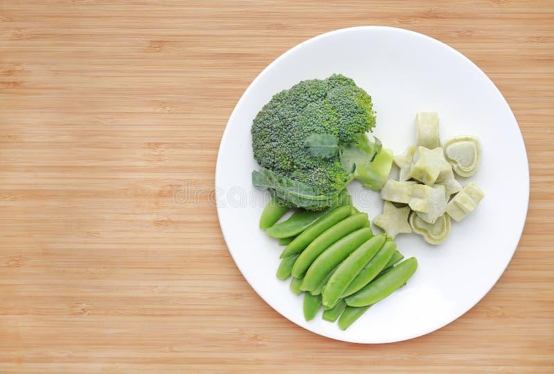 Ruw van het voedselbroccoli en schat van de groentenbaby in witte plaat met bevroren fijngestampt babyvoedsel eigengemaakt in wit royalty-vrije stock foto