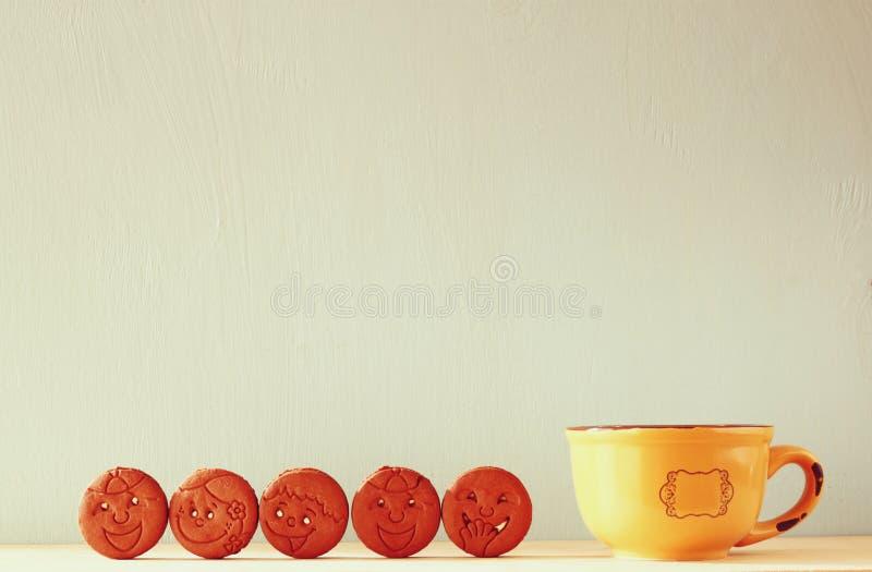 Ruw van koekjes met smileygezicht over houten lijst naast kop van koffie het beeld is retro gefiltreerde stijl royalty-vrije stock foto's