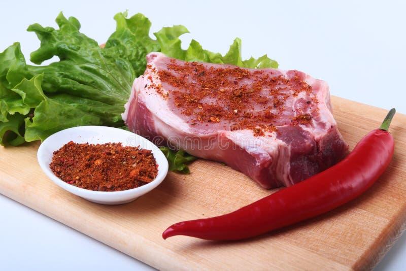 Ruw varkensvleeslapje vlees met kruiden, Spaanse peperpeper en kruiden op scherpe raad Klaar voor bbq stock foto's