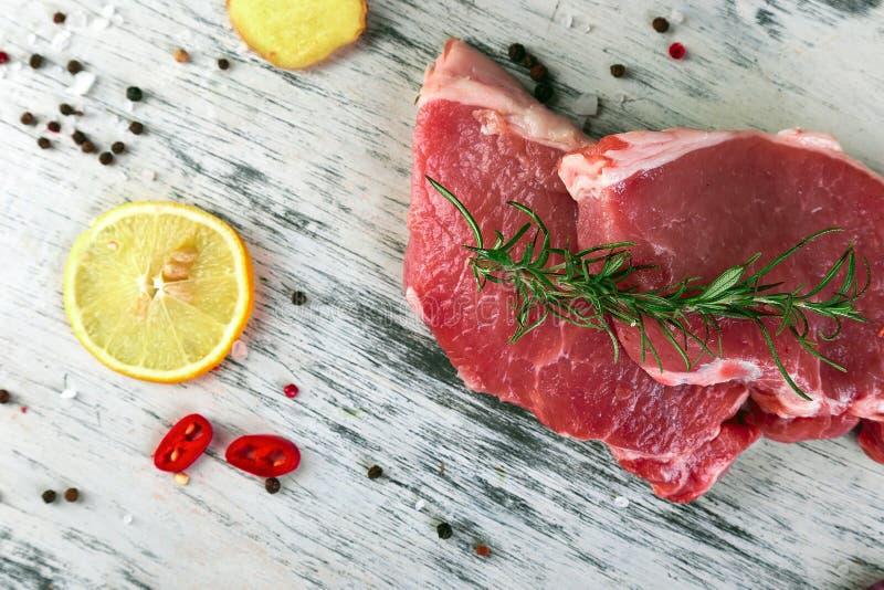 Ruw varkensvleesvlees op zwarte leiplaat met kruidingrediënt stock afbeeldingen