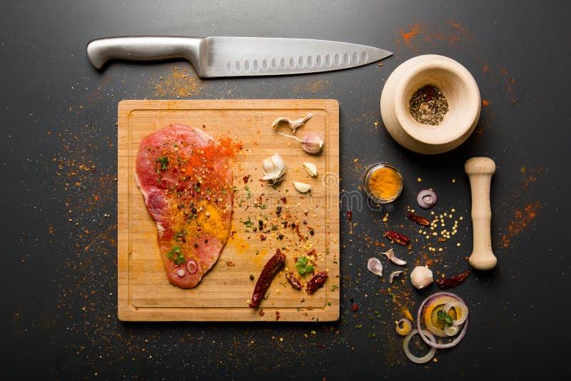Ruw vers varkensvleesvlees aan boord met specerijen op donkere achtergrond stock foto