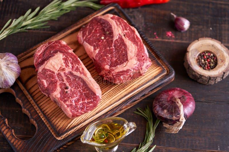 Ruw vers vlees riboogsteak op een houten snijplaat met rozemarijn, rode tomaten, peperkorrels, olijfolie, uien en knoflook stock foto's