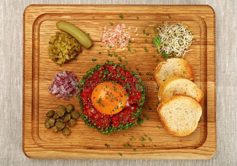 Ruw vlees tartare lapje vlees met eierdooier op houten raad stock afbeelding