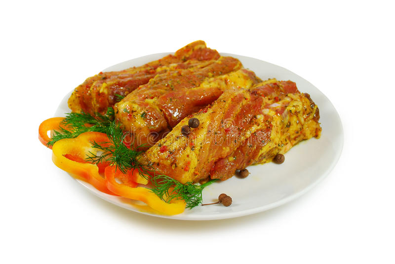 Ruw vlees Varkensvleesplakken met sause en verse die peper in een Schotel tegen Witte Achtergrond wordt geïsoleerd royalty-vrije stock afbeeldingen