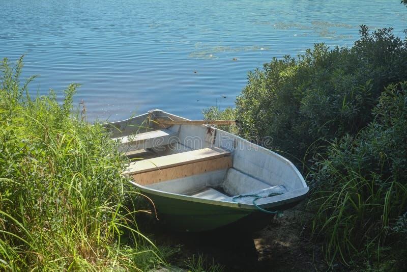 Ruwboot naast een meer met kruiden royalty-vrije stock fotografie