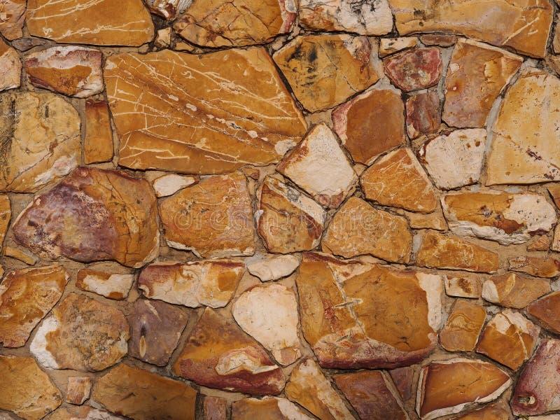 Ruwe bakstenen muur van aarde en steen gekleurde rotsen stock afbeelding