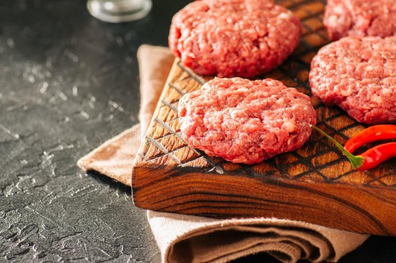 Ruwe burgers van het gehaktrundvlees op een houten raad Sluit omhoog en betrap stock fotografie