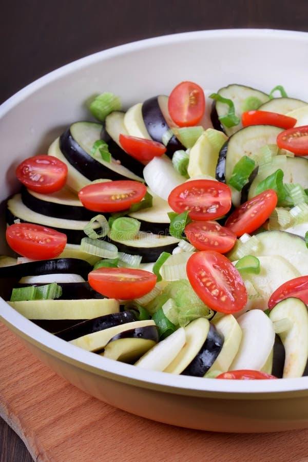 Ruwe courgette, aubergines en kersentomaten in een bakselschotel stock fotografie