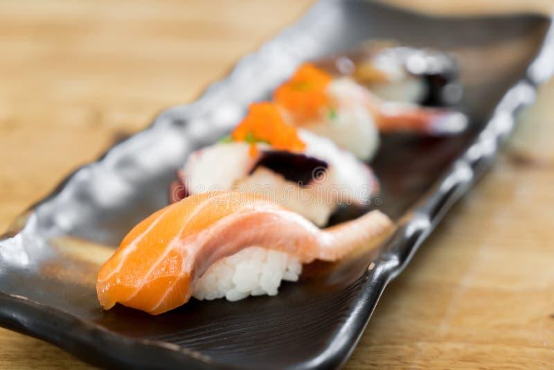 Ruwe de zalmsushi van Japan en verse mengelingssushi die in zwarte plaat - Japanse voedsel vastgestelde stijl bij Japans restaura stock afbeelding