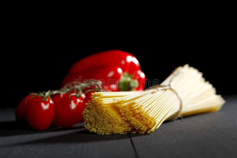 Ruwe deegwaren en groenten op zwarte lijst stock foto