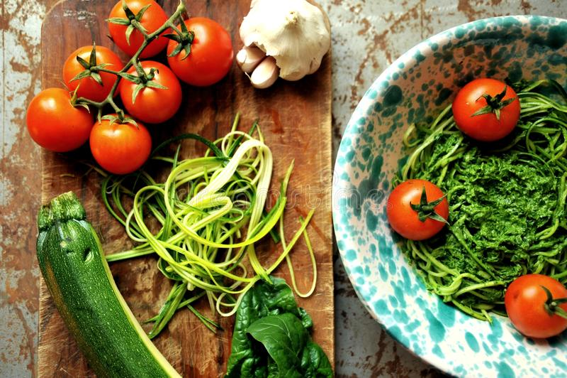 Ruwe deegwaren met courgette en spinaziepesto met tomaten royalty-vrije stock afbeelding