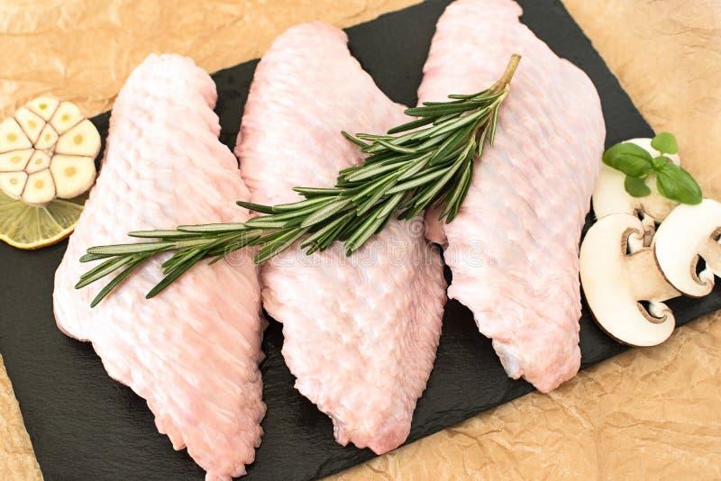 Ruwe delen van de vleugel van Turkije, drie stukken van kip, op een ronde houten scherpe raad met paddestoelen en rozemarijn op e stock foto's