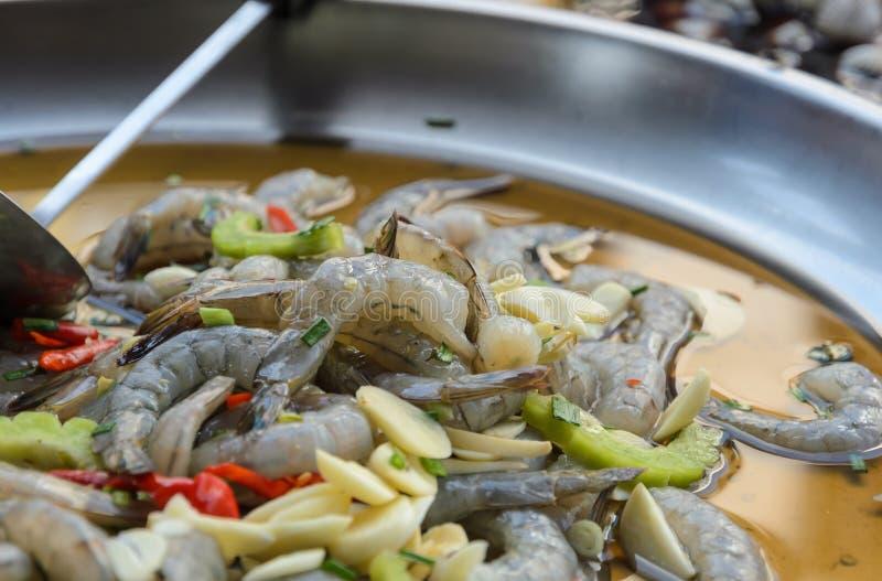 Ruwe die garnalen in kruidige vissensaus worden gemarineerd, Thaise keuken stock afbeelding