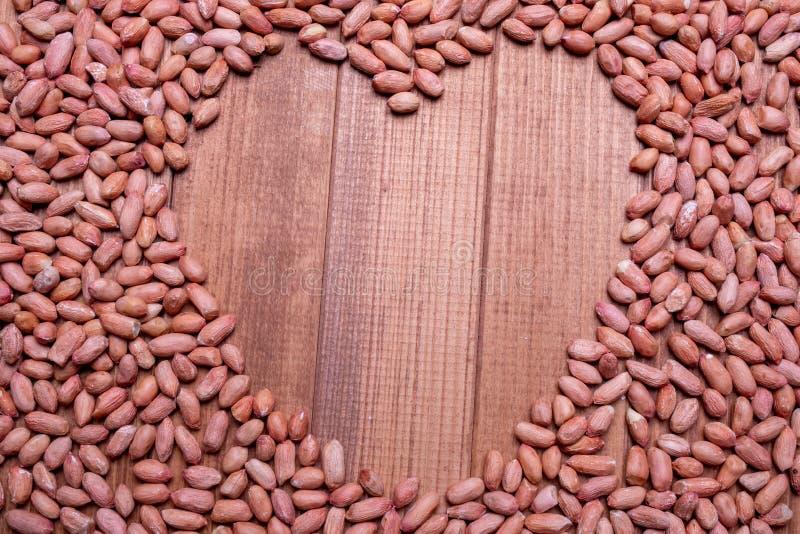 Ruwe die pinda's op een houten lijst worden verspreid De ruimte van het de close-upexemplaar van pindabonen in het midden stock foto's