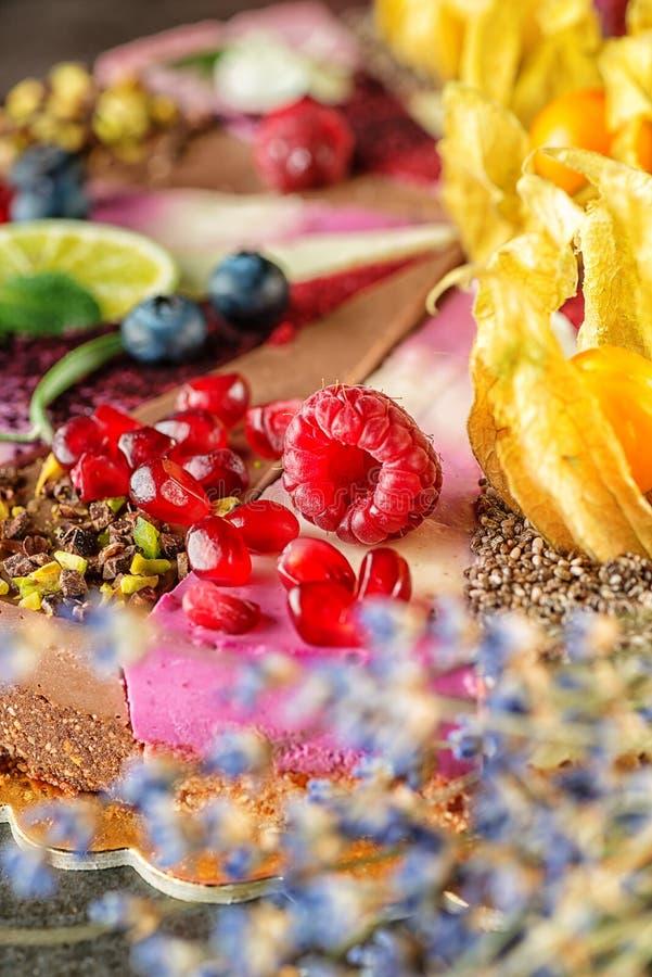Ruwe die veganistcakes met fruit en zaden, met bloem, productfotografie voor patisserie wordt verfraaid royalty-vrije stock foto's